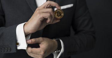 uomo elegante con bitcoin in mano